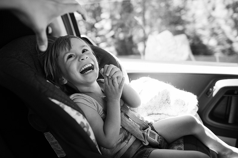 Smiling toddler on a road trip.