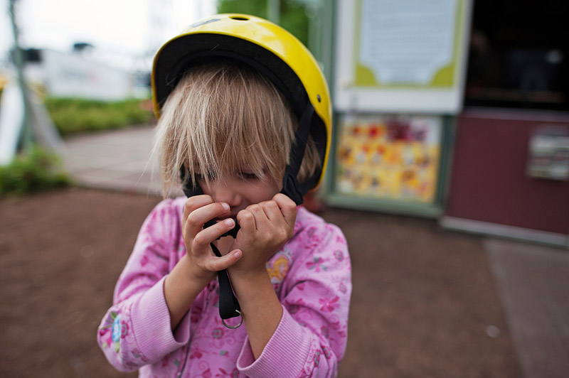 Girl putting on helmet.