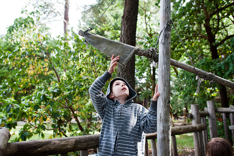 Boy playing in a pirate treehouse.