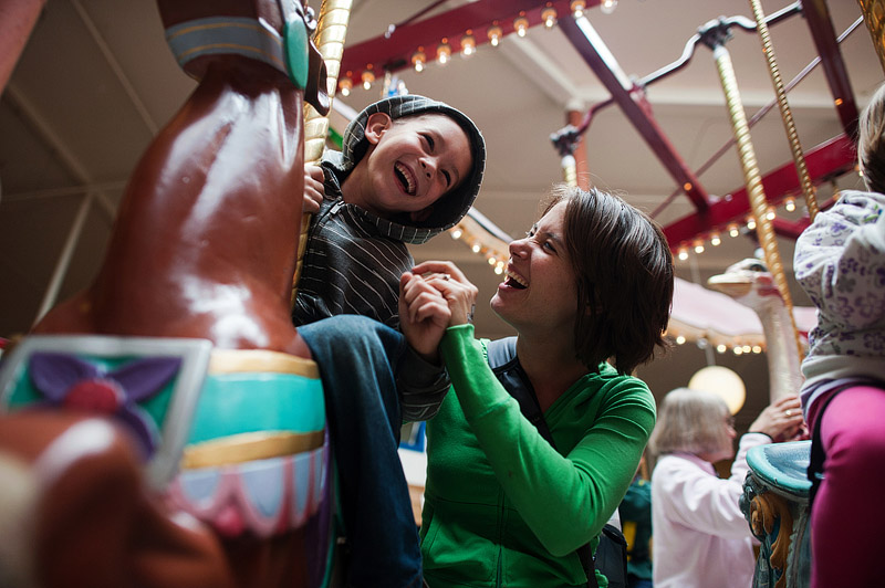 Mom and son laughing on the Seaside carousel.