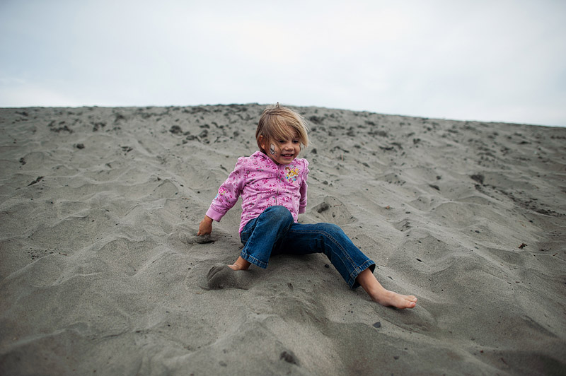 Girl sliding down the hill at Fort Stevens State Park.