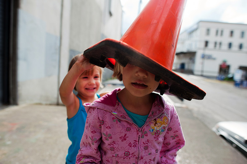 Little girl with construction cone on her head.