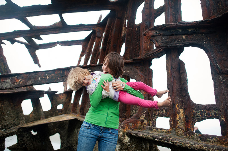 Mother tickling toddler at the Peter Iredale ship wreck in Oregon.