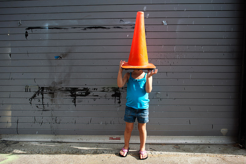 Toddler under a construction cone.