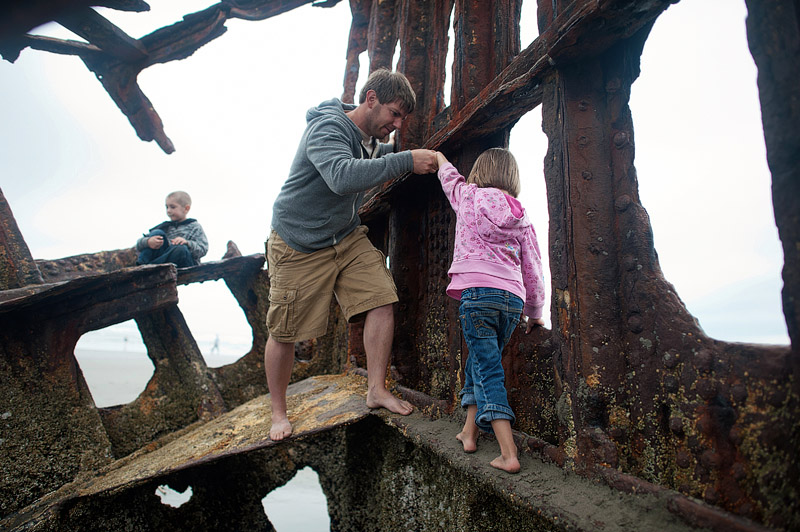 Father helping daughter walk up the Peter Iredale in Oregon.