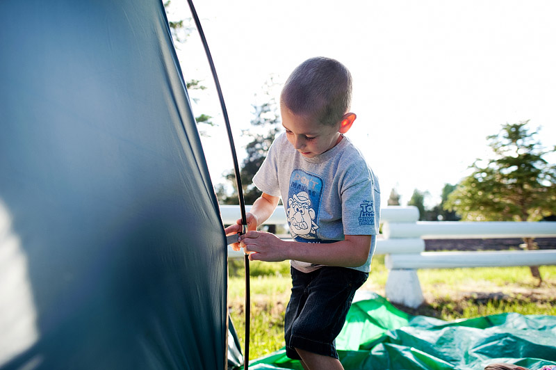 Boy anchoring tent.