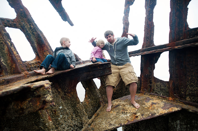 Father and kids in the Peter Iredale wrecked ship on the coast of Oregon.