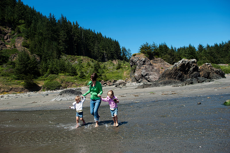 Mom and girls splashing in the Pacific Ocean.