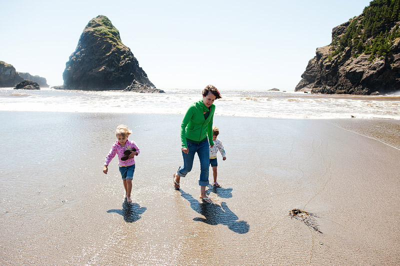 Family running from the cold Pacific ocean waves.