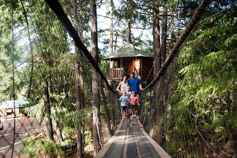 Family portrait in front of a treehouse.