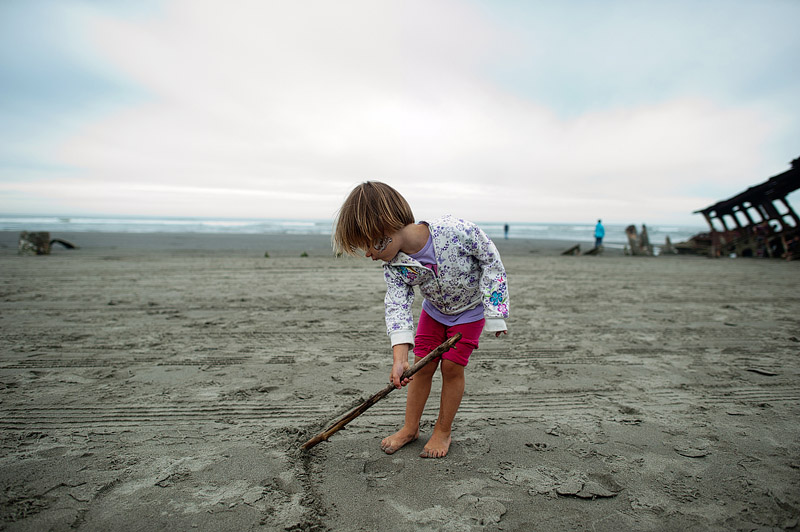 Girl drawing on the beach in Oregon with a stick.