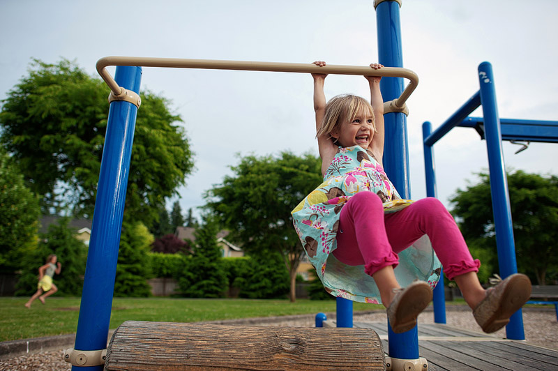 Little girl playing on rolling log at the park.