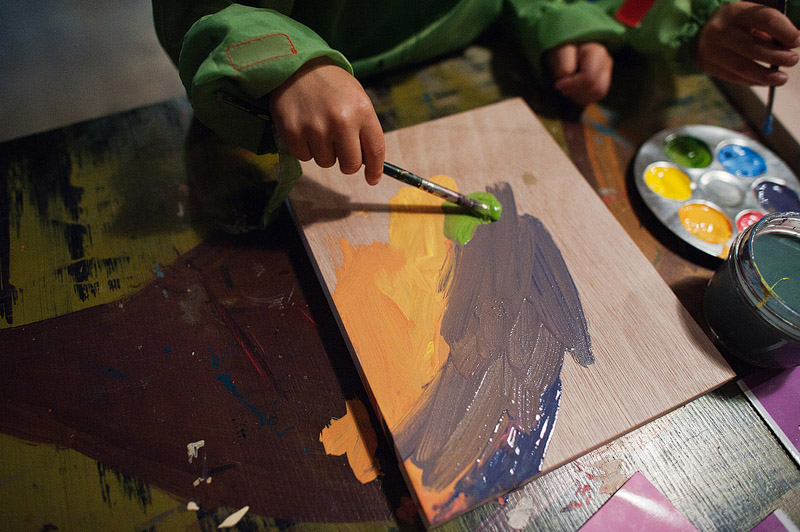 Toddler painting at the canvas.