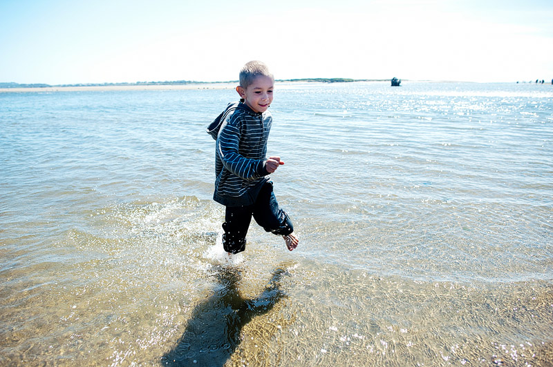 Boy running through waves.
