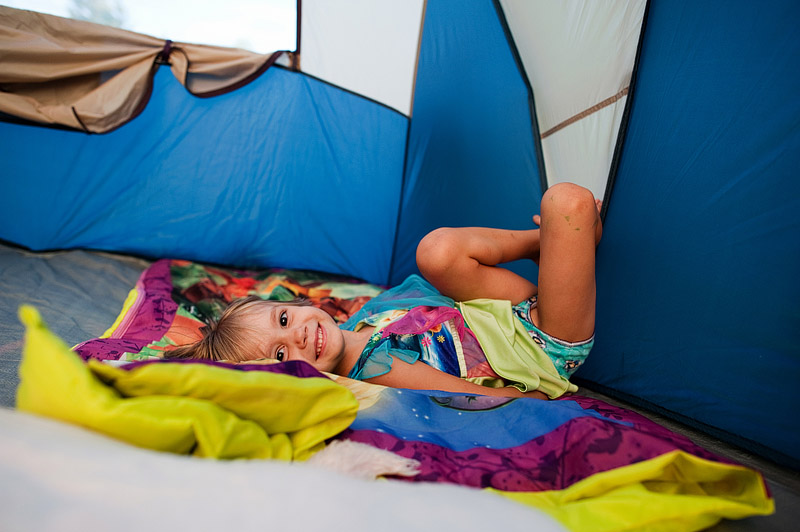 Little girl smiling in the tent.