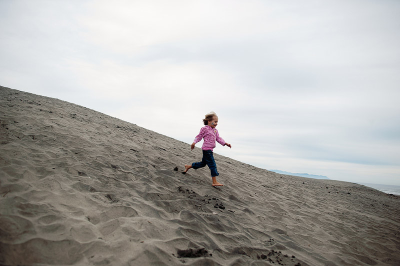 Girl running down the hill at Fort Stevens State Park.
