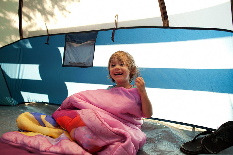 Girl plaing peekaboo in tent.