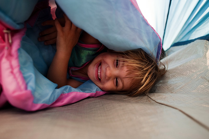 Litte girl laughing in sleeping bag.