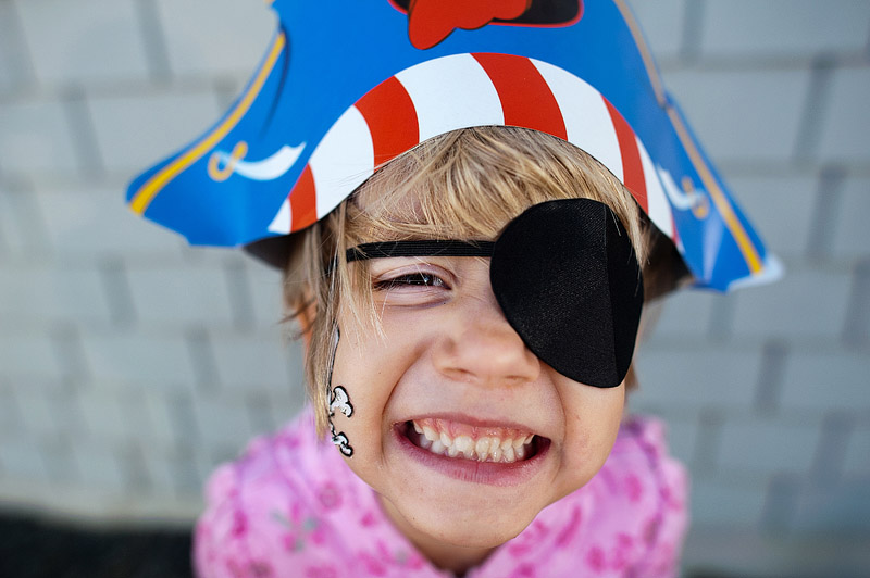 Girl with cheesy grin and eye patch.
