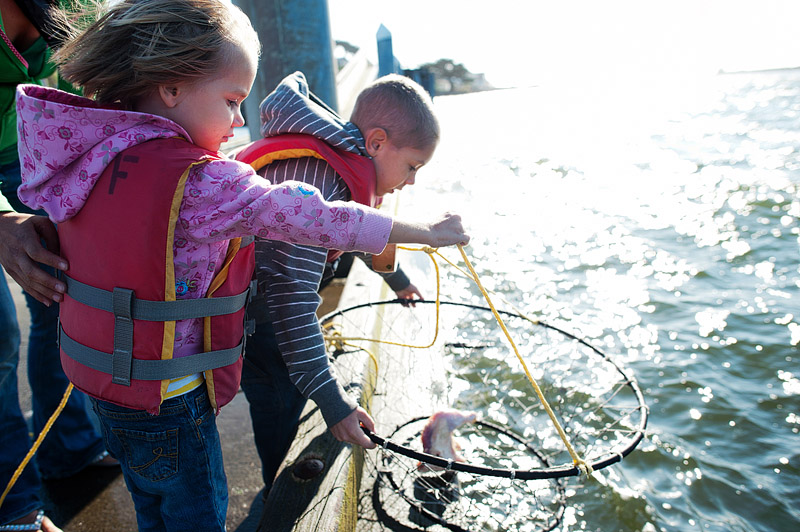 Brother and sister drop in net to catch crabs.