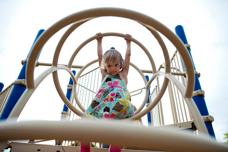 Girl climbing through play structure.