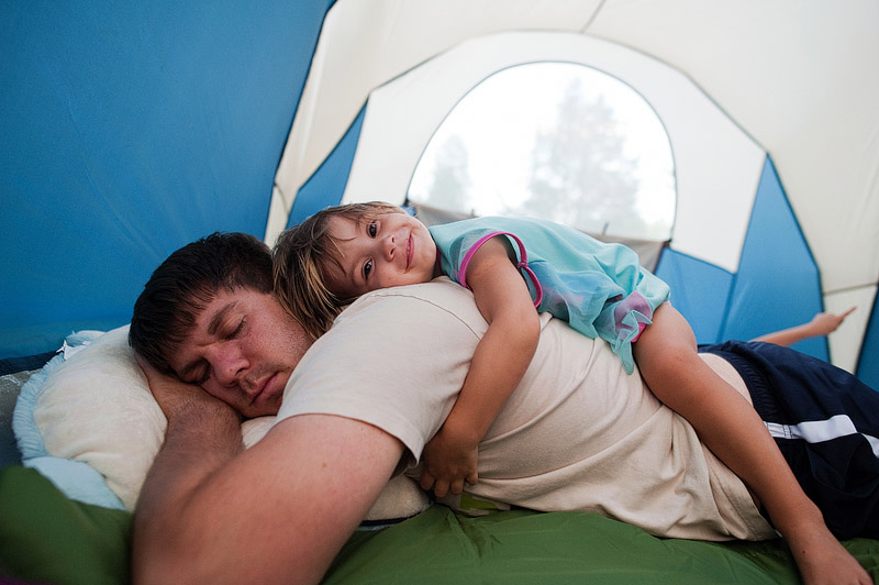 Girl laying on dad in tent.