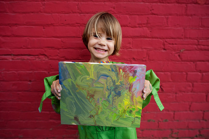 Toddler holding her painting she made at the canvas.