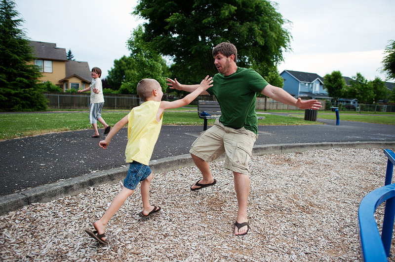 Boy playing tag with dad.