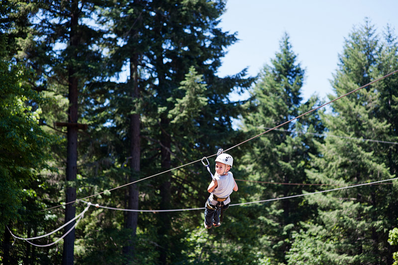 Boy riding a zip line at Out N About treehouses.