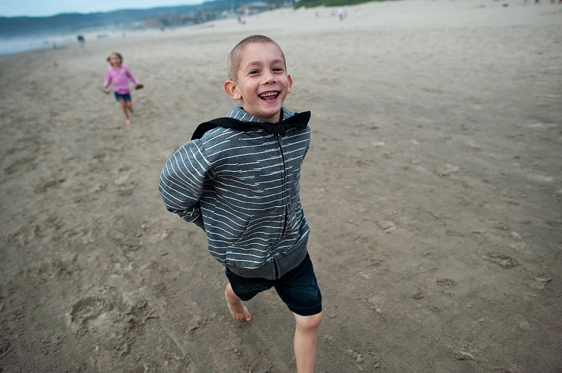 Kids running on Cannon Beach in Oregon.