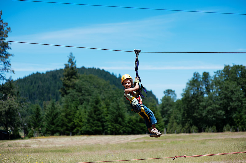 Toddler riding a zip line in Oregon at Out N About Treehouses.