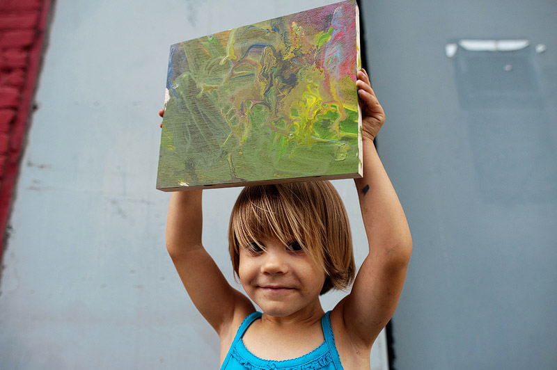 Toddler holding up her painting.