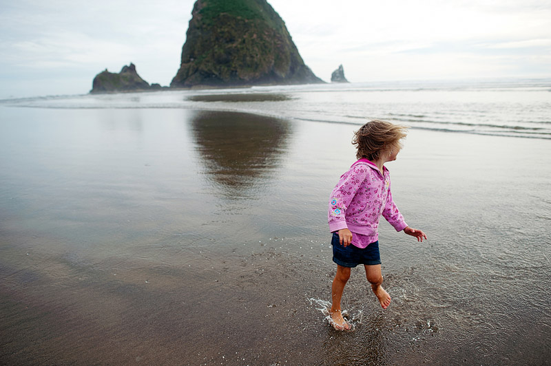 Girl spinning on Cannon Beach in Oregon.