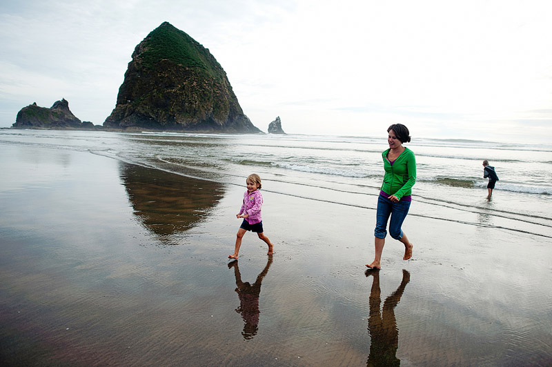 Family playing on Cannon Beach in Oregon together.