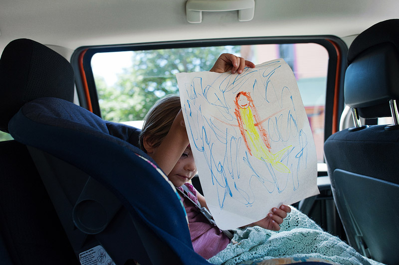 Toddler holding up a drawing.
