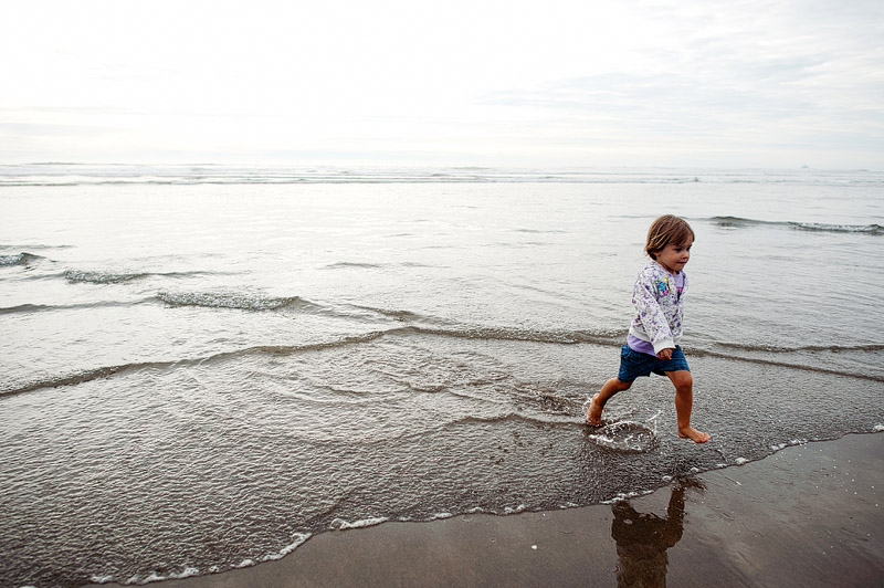 Toddler running from the waves in Oregon.