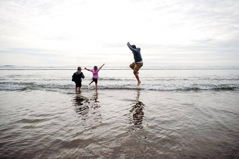 Family jumping in the Pacific Ocean together.