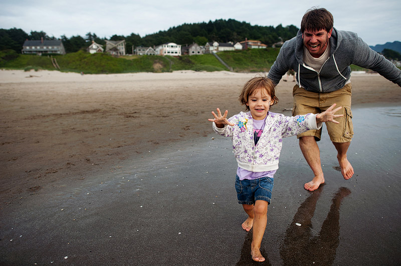 Father chasing daughter on the beach.