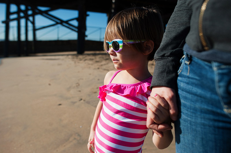Little girl holding her mom's hand by the Seal Beach pier.