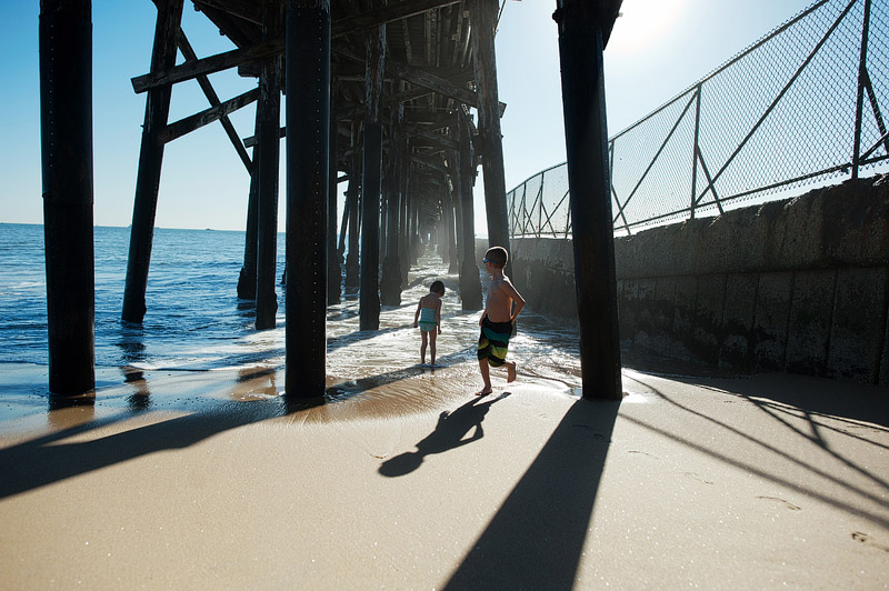 Kids playing under the Seal Beach pier.