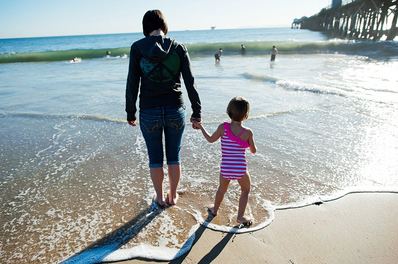 Mom and daughter playing in the Pacific Ocean waves.
