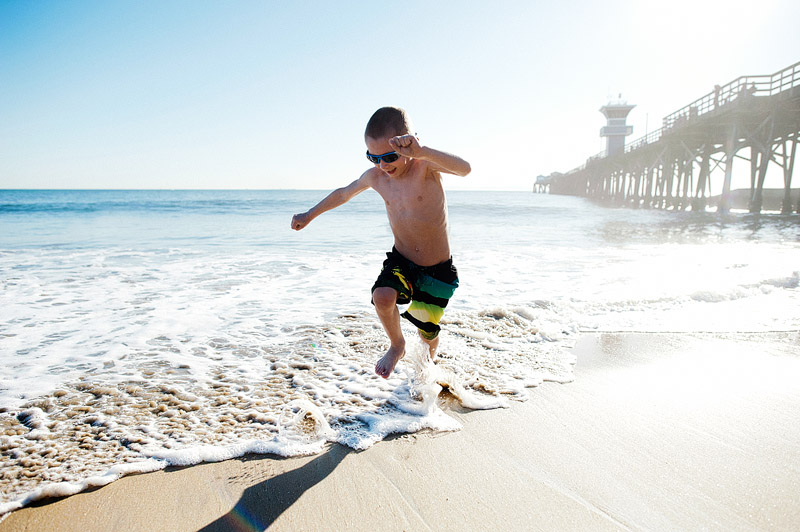 Boy jumping in the ocean waves.