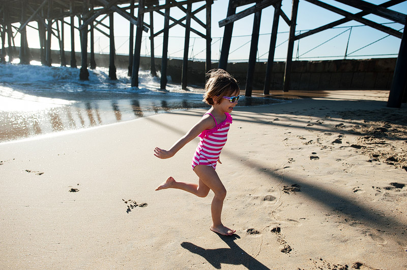 Girl running from the cold ocean water.