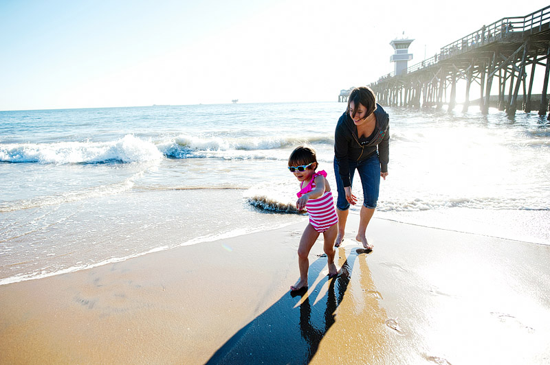 Mom and daughter playing in the ocean together.