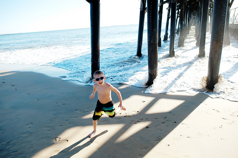 Boy playing under the Seal Beach pier.