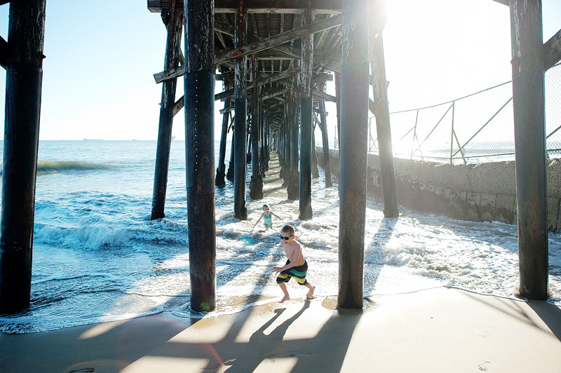 Boy playing under the pier.