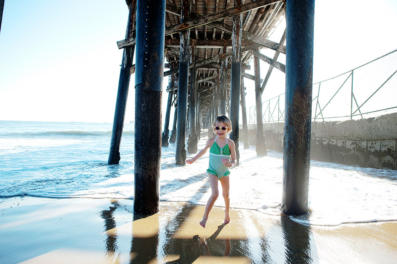 Girl playing under the Seal Beach pier.