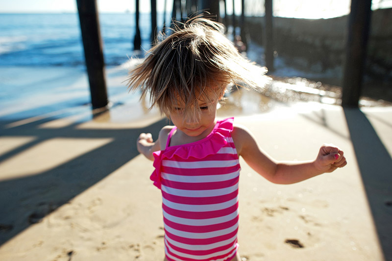 Girl rocking out by the ocean.
