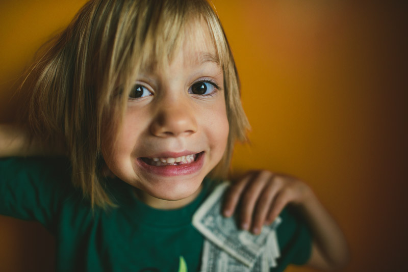 Kindergartener loses first tooth and gets five dollars from the tooth fairy.