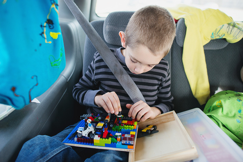 Kid building Legos in the car.